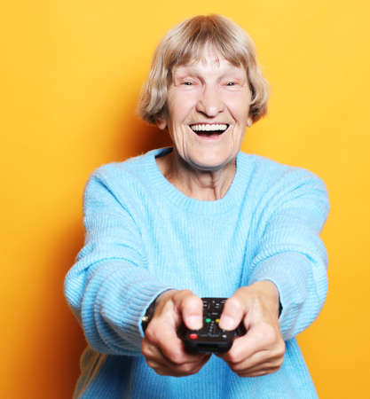 lifestyle, emotion and people concept: funny grandma is holding a TV remote over yellow background 免版税图像