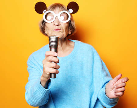 happy old woman with big eyeglasses holding a microphone and singing isolated on yellow background 免版税图像