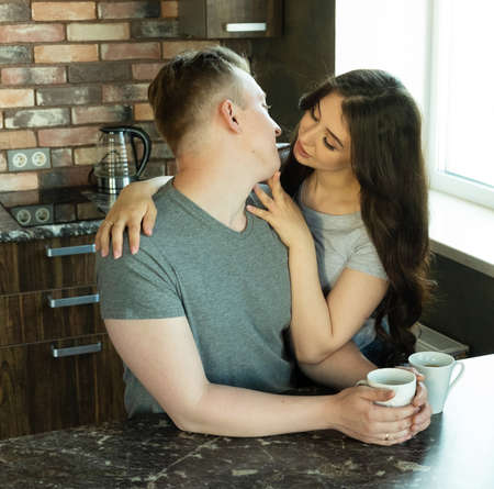 Young beautiful couple have breakfast in the early morning at home, hug, smile. Happy da for young family.