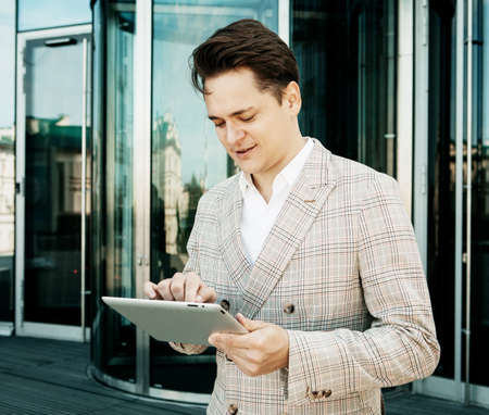 business, technology and people concept - young businessman with tablet over office building