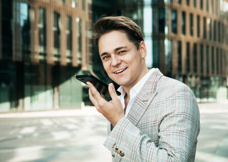business, technology and people concept - young businessman with smartphone over office building