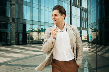 Young happy man in a business suit poses near a modern business center on a summer day