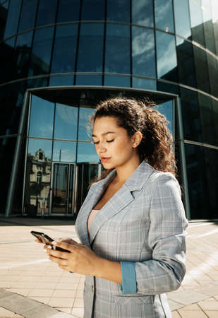 young business woman uses a mobile phone in front of a modern business center
