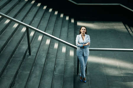 afro woman dressed in business style next to the stairs, business and career concept
