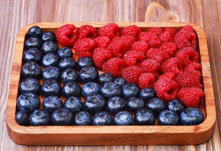 blueberries and raspberries on wooden plate 免版税图像