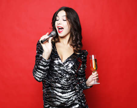 Young woman in black evening dress holding glass of champagne and microphone.