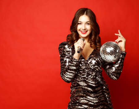 lifestyle and people concept - woman in evening dress holding microphone and disco ball 免版税图像