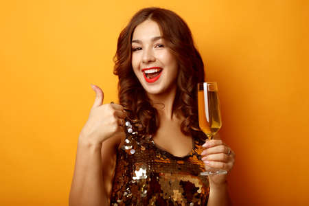 woman in evening dress holding glass of champagne over yellow background 免版税图像