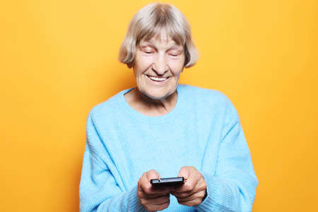 old woman wearing blue sweater talking on cell phone 免版税图像