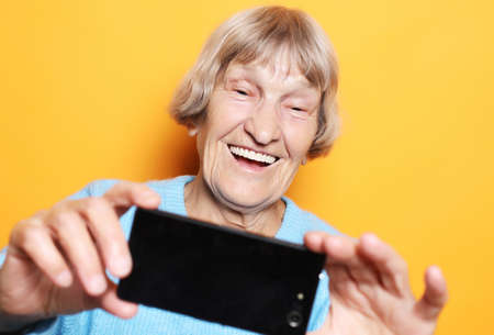 lifestyle, tehnology and people concept: grandma smiles and takes a selfie over yellow background