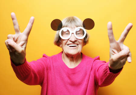grandmother wearing pink sweater and big sunglasses over yellow background. 免版税图像