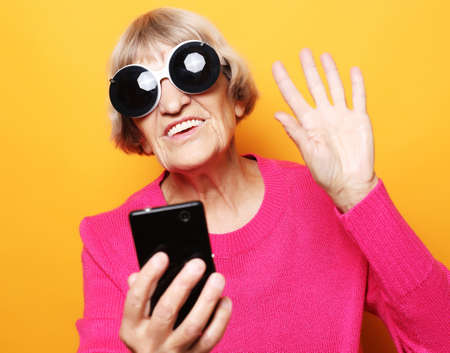 old grandmother is talking to her grandchildren by phone, smiling and greeting them.Close up.