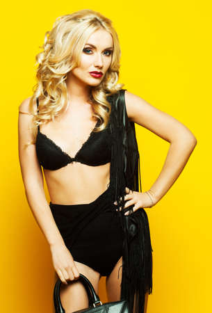 fashion and people concept: beautiful woman with luxurious blond hair in lingerie posing over yellow background