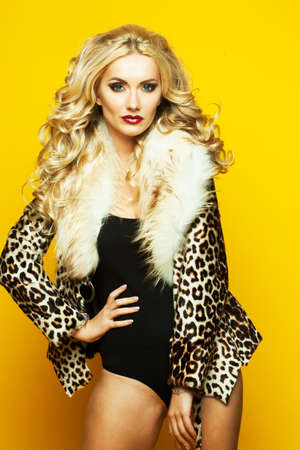 fashion and people concept: beautiful sensual woman with luxurious blond hair in lingerie and fur coat posing over yellow background