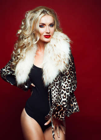 Beautiful fashionable woman with blond hair, dressed in a leopard jacket, holds a bag and poses on a red background. 免版税图像
