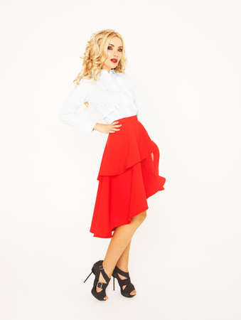 Blond fashion model with luxury hair and red skirt in studio over white background