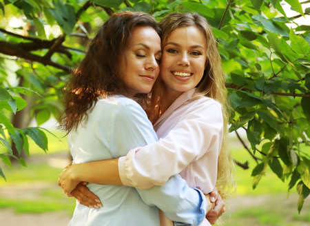 lifestyle and people concept: mature mother and adult daughter hugging in the park on a summer day