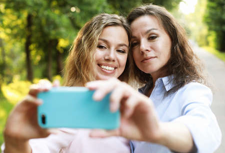 mature mother and adult daughter are doing selfie by mobile phone in summer park