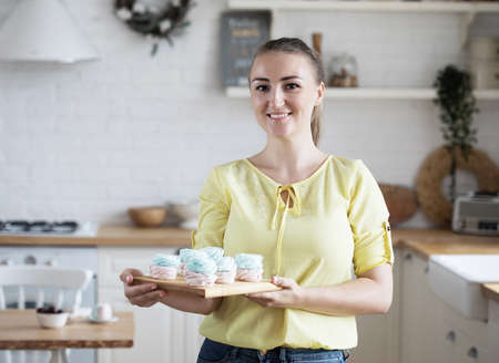 Young baker woman holding pastries. Happy, smiling and cheerful. 免版税图像