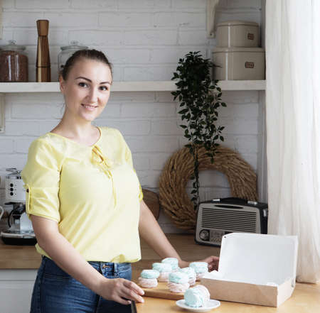 Young cook woman packs pastries in a box. Small home business.