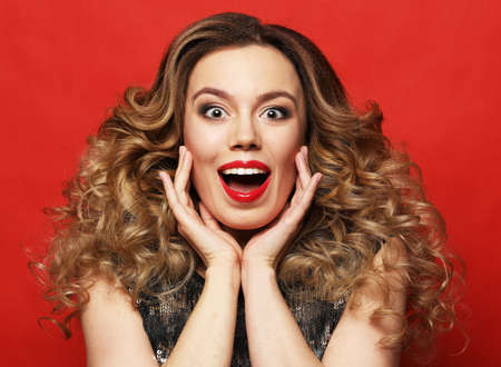 Surprised blonde woman with long wave hair wearing evening dress with opened mouth over red background.