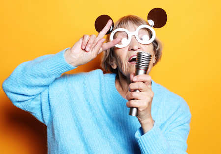 happy old woman with big eyeglasses holding a microphone and singing isolated on yellow background Фото со стока
