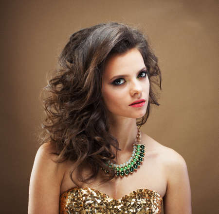 Brunette girl with long and shiny curly hair . Beautiful model woman with curly hairstyle.