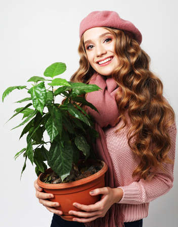 Attractive young blond woman standin and holding flower in pot over gray background