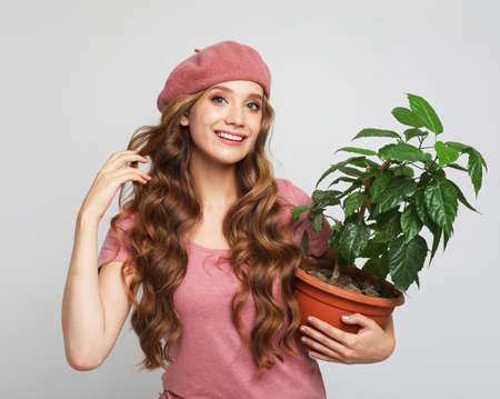 Attractive young blond woman standin and holding flower in pot over gray background Standard-Bild