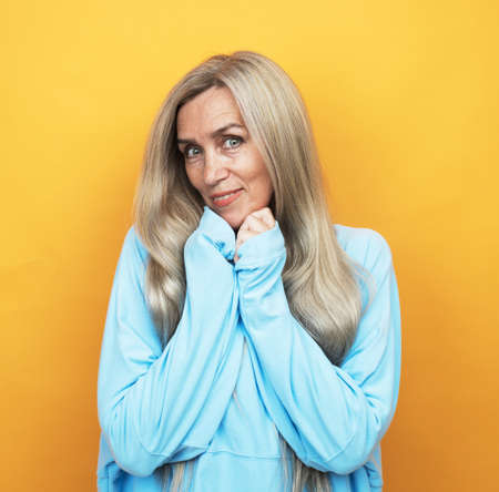 Portrait of charming lovely grandparent woman with long hair enjoy rest relax wear good look blue pullover isolated over yellow background. Lifestyle concept.