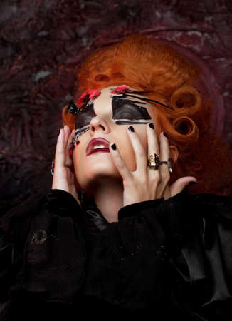 Red-haired young woman in witch costume. Creative makeup for masquerade. Halloween and party concept.