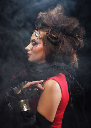 Young brunette woman with creative makeup and and hairdo posing on dark background. Party time and halloween.