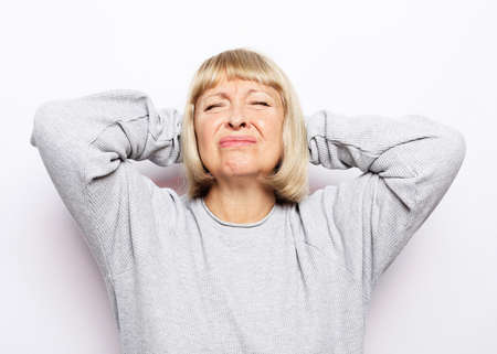 Lifestyle, health and old people concept: Beautiful mature woman touching her head having a headache, on white background