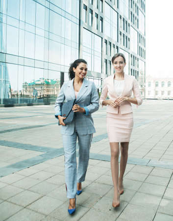 Business, people and lifestyle concept: two office workers standing together outdors near modern business building. Positive emotions. Summer day,