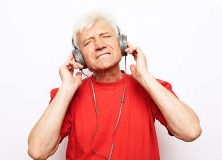 Lifestyle, tehnology and old people concept: elderly gray-haired man witj closed eyes wearing red t-shirt listening to music with headphones over white backgrund