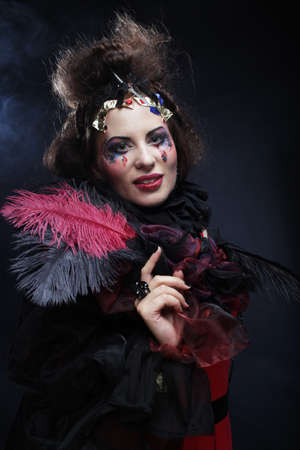 Party time and halloween. Young fashionable woman with creative makeup and hairstyle posing on dark background.