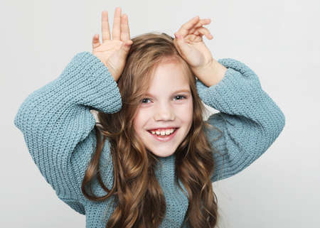 ? ute little girl plays with friends. Happy child shows horns over white background. Emotion and people concept. 版權商用圖片