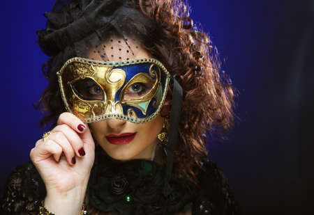 Portrait of curly woman with artistic make-up holding mask