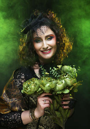 Young curly woman with brigt visage holding big green flowers, fairy tale and fashion concept. 免版税图像