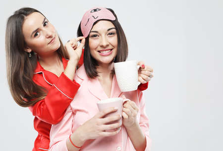 Two beautiful young women dressed in pajamas holding a cups, hugging and smiling. Imagens