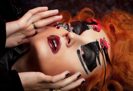 Gothic witch. Dark woman. Halloween picture. Red-haired woman with bright make up.
