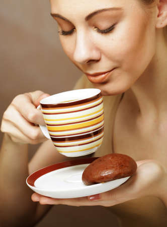 Beautiful woman drinking coffee. Photo of young blond girl holding a cup with coffee over beige background. Close up.