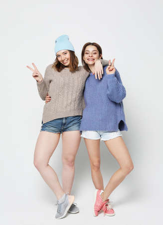 A full-length portrait of two smiling girls dressed in hipster style showing v-sign. Imagens