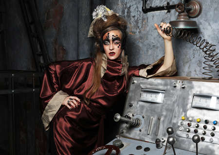Beautiful young woman with bright makeup and hairstyle, creative costume. Steampunk party style.