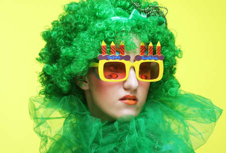 Young woman with green wig and big party glasses. Holiday theme. Banque d'images