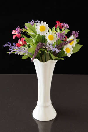 Artificial flowers in a white vase. A bouquet of artificial flowers in a white vase on a black background. 免版税图像
