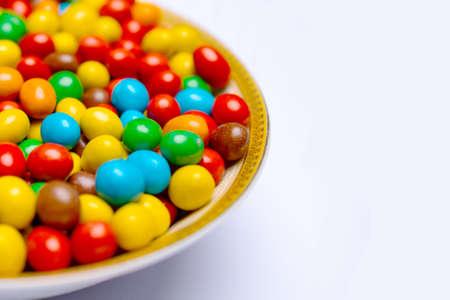 Image of colored round sweets on the plate. Background of small multicolored dragees on the plate. Closeup. Side vew.