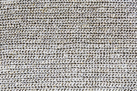 Texture of a knitted fabric of white color closeup, machine knitting. Knitted jersey background with a relief pattern. Background