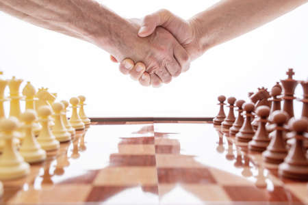 Image of shaking hands over chess. World Chess Day. International Chess Day. July 20. Side view. White background. Focus on the hands.