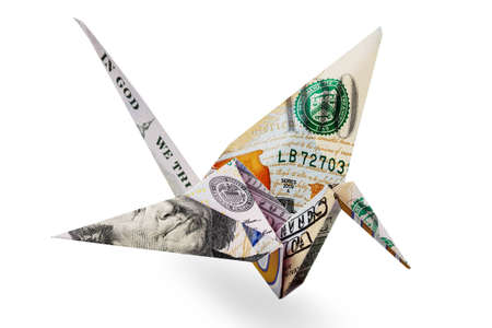 Origami crane made of one hundred dollar bill. Origami crane made of money. Concept represents money's ability to just fly away. Isolate on white background. Close-up. Side view